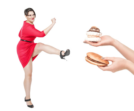 Beautiful plus size woman fighting off unhealthy food isolated on white background Standard-Bild