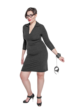 handcuffed: Beautiful plus size woman in black dress with handcuffs isolated on white background