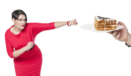 beating: Beautiful plus size woman in red dress beating cake isolated on white background