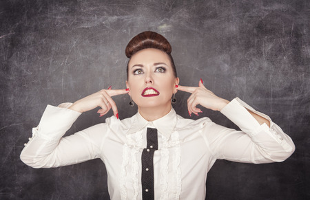 deafening: Beautiful woman with fingers in her ears on the blackboard background