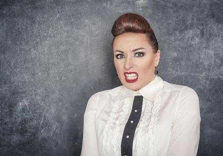 revulsion: Scared teacher woman in white blouse on the blackboard background Stock Photo