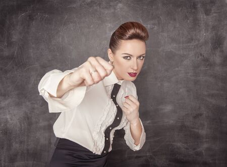 power symbol: Teacher woman beating with her fists on the blackboard background