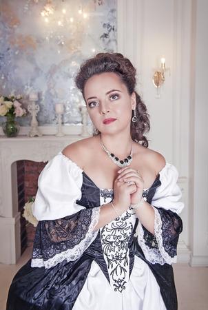 middeleeuwse jurk: Mooie jonge vrouw in het zwart en wit lang middeleeuwse kleding