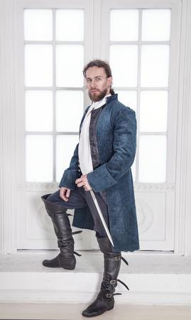 Jonge knappe man in middeleeuwse kleding met zwaard staan in de kamer Stockfoto