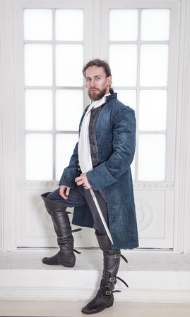 Young handsome man in medieval clothes with sword standing in the room Stock Photo