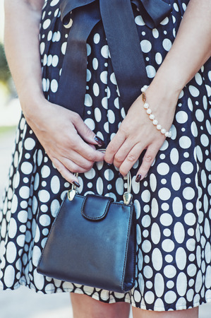 designer bag: Fashionable woman with small bag in her hands and dress outdoor
