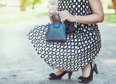 designer bag: Fashionable woman with small bag in her hands and dress sitting outdoor