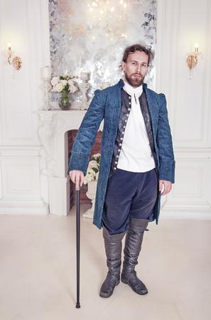 Mladý pohledný muž ve středověkých šatech stojí v pokoji