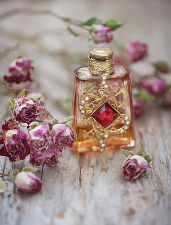 Dry tea roses and vintage perfume bottle on the old wood background