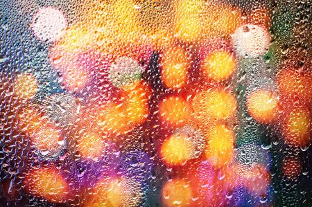 rain: Drops of rain on glass with defocused lights. Abstract colorful blurred background