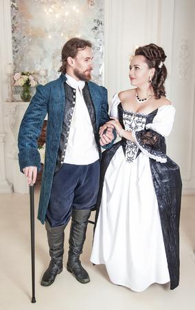 vestido medieval: Pares de la mujer hermosa y el hombre en ropa medieval en la sala de Foto de archivo