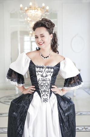 vestido medieval: Joven y bella mujer en blanco y negro y largo vestido medieval guiño Foto de archivo
