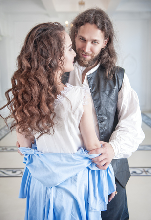 Handsome man in medieval costume undress beautiful woman with long hair