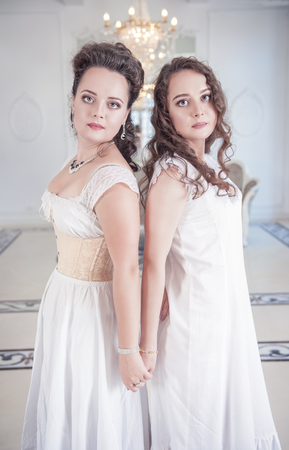 Two beautiful young woman in old-fashioned negligee