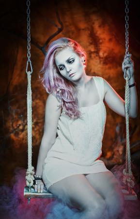 dead woman: Sad dead woman in Halloween style sitting on the seesaw