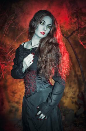 jolie fille: Belle sorci�re aux cheveux longs sur fond Halloween