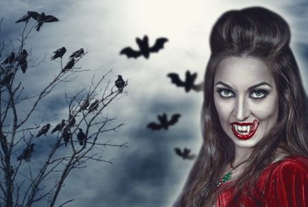 long tongue: Beautiful witch with long tongue on Halloween background Stock Photo