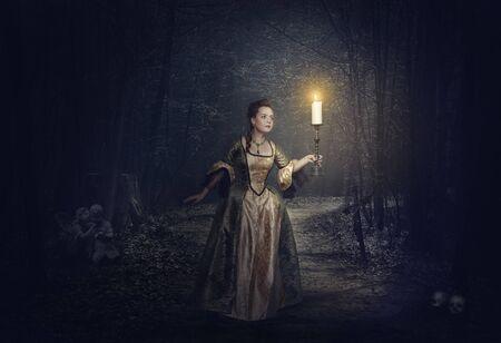 medieval dress: Hermosa mujer con la vela en alineada medieval en el camino de niebla. Paisaje de Halloween