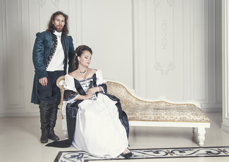 victorian girl: Beautiful couple woman and man in medieval clothes in the room Stock Photo