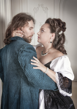 pompous: Beautiful couple woman and man in medieval clothes hug Stock Photo