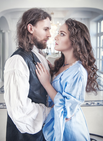 Beautiful passionate couple woman and man in medieval clothes in the room