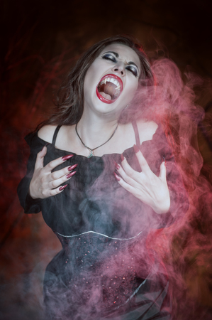 sexy devil: Screaming halloween beautiful vampire with long hair in smoke