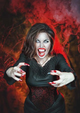 long nails: Angry halloween beautiful vampire with long nails holding out hands Stock Photo