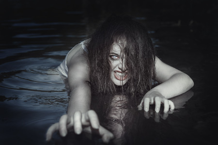 scared woman: Young beautiful drowned ghost woman in the water outdoor