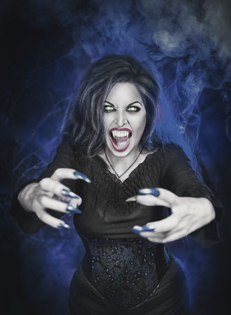 unas largas: Angry hermosa vampiro de Halloween con las u�as largas tendi�ndole las manos Foto de archivo