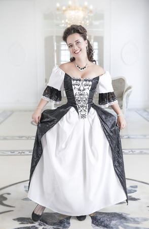 an obeisance: Beautiful young woman in black and white long medieval dress making curtsey