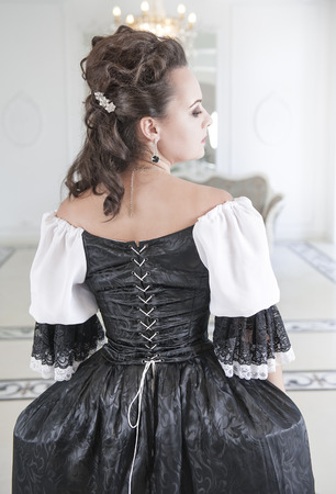 Beautiful medieval woman in long black and white dress, back