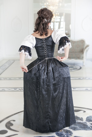 ruche: Beautiful medieval woman in long black and white dress, back