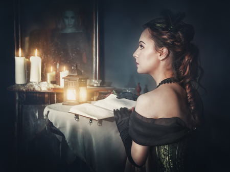 gothic girl: Beautiful woman with book in retro dress and ghost in the mirror