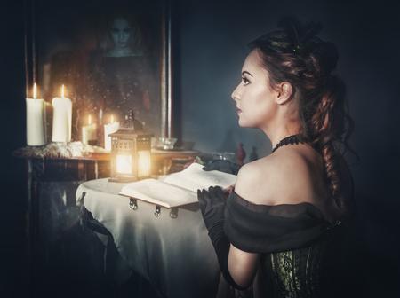medieval dress: Mujer hermosa con el libro en el vestido retro y el fantasma en el espejo