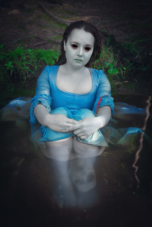 ghost face: Beautiful dead ghost woman sitting in the water Stock Photo