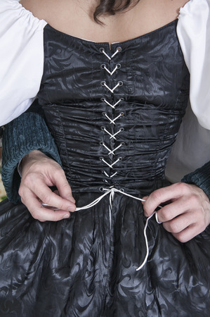 Man hands untying corset of woman in black medieval dress Banco de Imagens