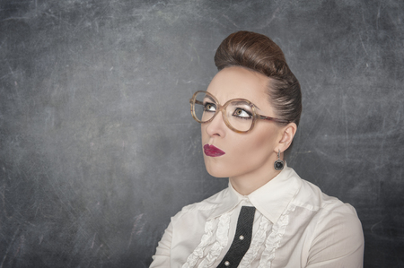 Woman in eyeglasses looking on something at the blackboard background