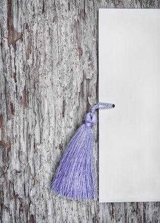 fringe: Wooden grunge background with paper and tassel fringe