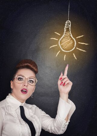 afflatus: Idea concept. Woman showing on lamp on the blackboard background