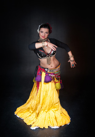 girl on a beautiful background: Beautiful exotic belly tribal dancer woman on black background Stock Photo