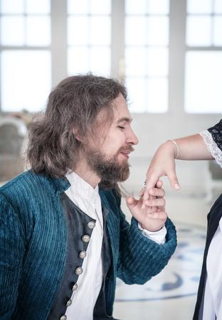 parejas romanticas: Hombre hermoso en alineada medieval besar la mano de la mujer hermosa Foto de archivo