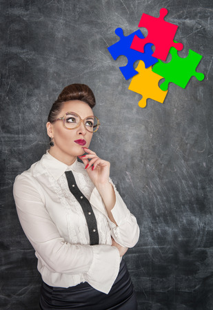 afflatus: Business Idea concept. Woman looking on puzzle on the blackboard background Stock Photo