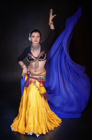 smile girl: Beautiful exotic belly tribal dancer with blue shawl woman on black background
