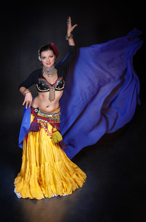exotic dancer: Beautiful exotic belly tribal dancer with blue shawl woman on black background