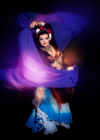 tänzerin: Schöne exotische Bauch Stammes-Tänzerin Frau mit blauen Schal auf schwarzem Hintergrund