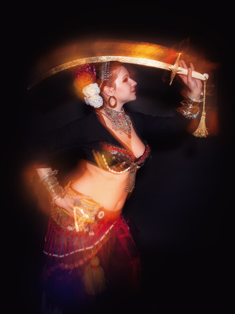 exotic dancer: Beautiful exotic belly tribal dancer woman with sword on black background