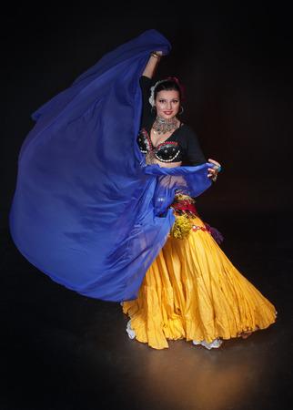 black girl: Sch�ne exotische Bauch Stammes-T�nzerin Frau mit blauen Schal auf schwarzem Hintergrund