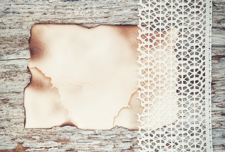 paper board: Lace fabric and aged paper on the old wooden background Stock Photo