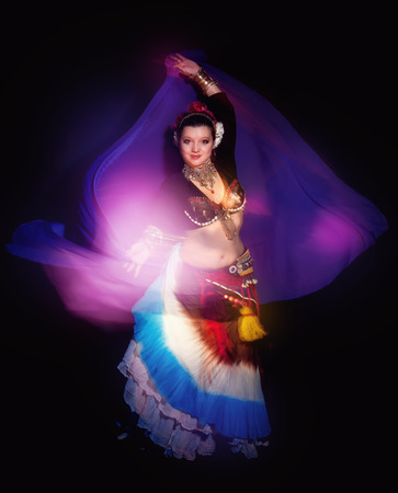 sexy asian woman: Beautiful exotic belly tribal dancer woman with blue shawl on black background