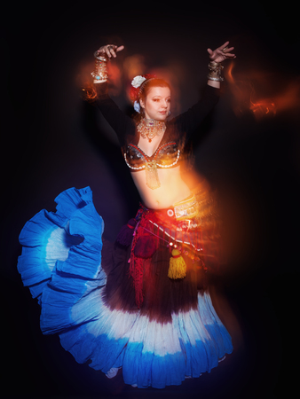 action girl: Beautiful exotic belly tribal dancer woman on black background Stock Photo